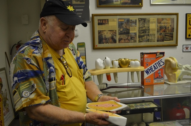 Peter Sidlow shows off the inside of a vintage dental teaching tool, among antiques he stocks at Peter J. Sidlow — Advertising Antiques in the back room of The Ribbon Store, 572 S. Decatur Blvd. ...