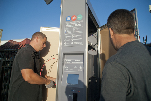Viktor Schrecengost, left, and Jonny Cobb work to install a new bike-sharing station near Fremont Street and Maryland Parkway in downtown Las Vegas on Friday, Sept. 23, 2016. The Regional Transpor ...