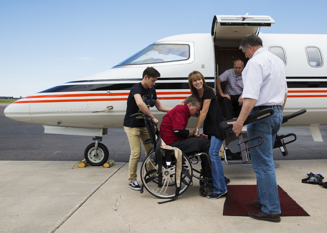 Sam Schmidt, middle, is helped off a charter flight by wife Sheila, right, and son Spencer on Thursday, June 9, 2016, in Colorado Springs, Colo. Schmidt, owner of IndyCar team Schmidt Peterson Mot ...