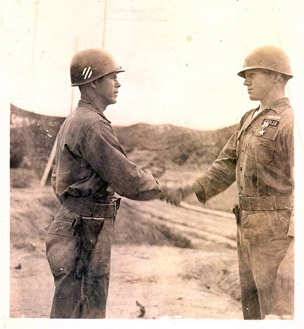 Pvt. Warren Sessler, right, shakes hands with 3rd Infantry Division signal officer Col. Stephan Morris after Morris pinned the Silver Star medal on his uniform on Aug. 25, 1953 outside the divisio ...