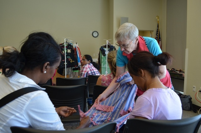 Sherry Eames shows Sit 'n' Sew participants a step-by-step sample during Lois Campbell's lesson on crafting aprons from men's button-up dress shirts. Windmill Library, 7060 W. Windmill Lane, welco ...