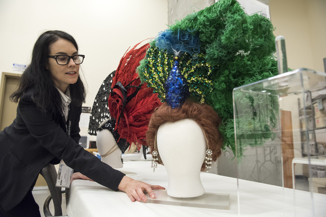 """Karan Feder, guest curator of costumes and textiles, handles a head dress from """"The Les Folies Bergere"""" exhibit at the Nevada State Museum Aug. 27. Martin S. Fuentes/View"""