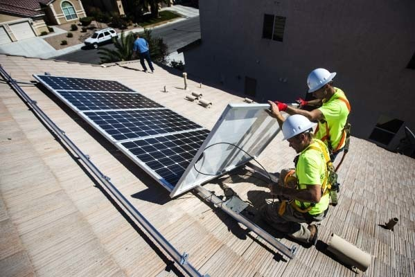 Jacy Sparkman, left, and Matt Neifeld with Robco Electric install solar panels at a home in northwest Las Vegas. (Jeff Scheid/Las Vegas Review-Journal)