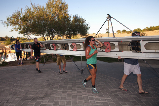 Kate Capistran, center, a member of the 2013 Atlantic 10 Conference Championship team at University of Rhode Island, helps load a racing shell with her crew mates after a workout at Lake Las Vegas ...