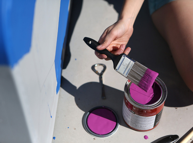 Tatiana Hantig dips her brush in magenta paint while painting a utility box in the pattern of a desert tortoise outside of Desert Breeze Park Community Center Oct. 21, 2013, in Las Vegas as part o ...