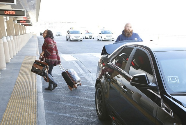 Ride-hailing company Uber driver Mike Difiore, right, of Las Vegas drops his rider off at McCarran International Airport at Terminal 3 on Tuesday, Dec. 8, 2015. Bizuayehu Tesfaye/Las Vegas Review- ...