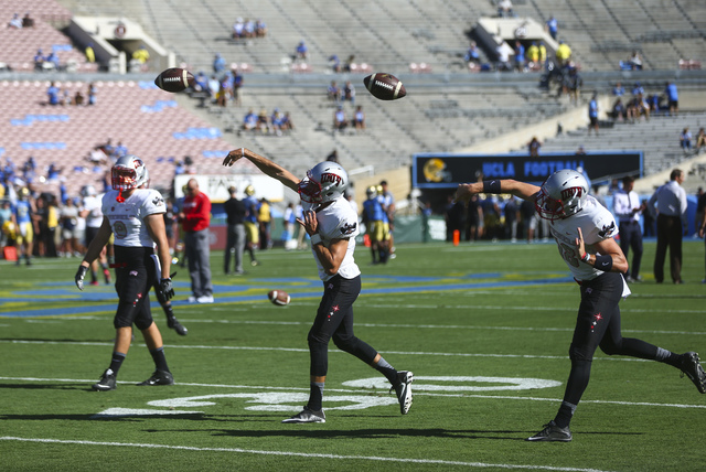 UNLV Rebels quarterback Kurt Palandech (14), center, and UNLV Rebels quarterback Dalton Sneed (18), right, warm up ahead of a football game against UCLA at the Rose Bowl in Pasadena, Calif. on Sat ...