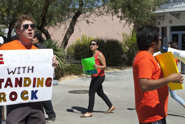 Protesters from NextGen Climate Evan Livingston, from left, Rubi Martinez and Don Naque gather outside of University of Nevada, Las Vegas to stand in solidarity with Standing Rock Sioux tribe on T ...