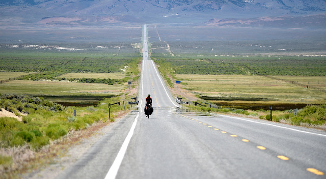 Noah Sorensen of N. Y. rides his bicycle as he continues a cross county trip along the long and straight pavement of U.S. Highway 50 west of Austin, Nev. Wednesday, July 13, 2016. Since a 1986 Lif ...