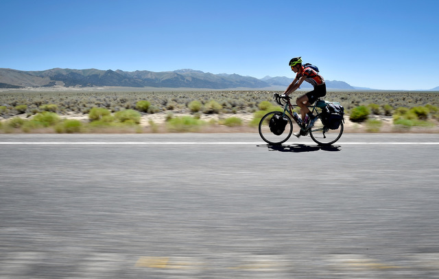Noah Sorensen of N. Y. rides his bicycle as he continues a cross county trip along U.S. Highway 50 west of Austin, Nev. Wednesday, July 13, 2016. Since a 1986 Life magazine which dubbed the Nevada ...