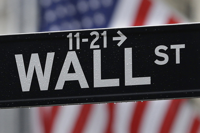 This July 9, 2015 photo shows a Wall Street sign near the New York Stock Exchange in New York.  Stock rose and the dollar fell on Friday, Sept. 2, 2016,  after a key report showed the U.S. economy ...