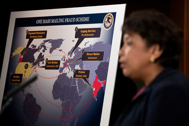 A visual aid of mass mailing fraud is displayed as Attorney General Loretta Lynch, foreground, speaks at a news conference at the Justice Department in Washington, Thursday, Sept. 22, 2016, to ann ...