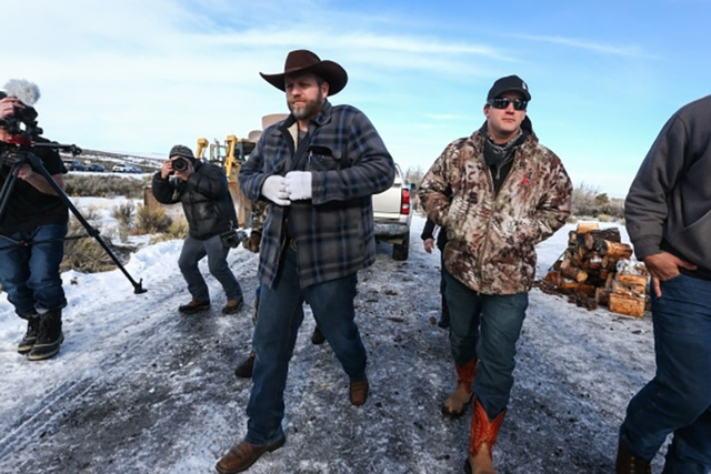 Ammon Bundy, center left, arrives to speak at a news conference by the entrance of Malheur National Wildlife Refuge headquarters near Burns, Ore., on Wednesday, Jan. 6, 2016. (Chase Stevens/Las Ve ...