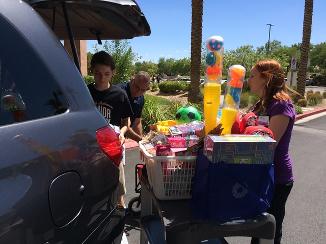 Jack Murphy and his father, Patrick, unload toys from the family's SUV Aug. 11 at Summerlin Hospital as Jacquie MacLeod, child life specialist, watches. Jan Hogan/View