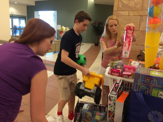 Faith Lutheran High School student Jack Murphy, 15, second from right, and his mother, Wendy, far right, unpack toys Aug. 11 at Summerlin Hospital. Helping them, far left, is Jacque MacLeod, a chi ...
