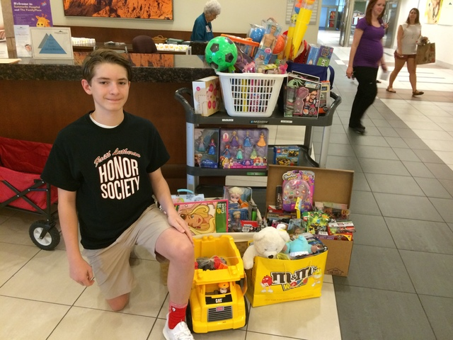 Jack Murphy pauses Aug. 11 beside the toys he donated to Summerlin Hospital's Pediatric Unit. He collected 144 toys as part of a National Honors Society project. Jan Hogan/View