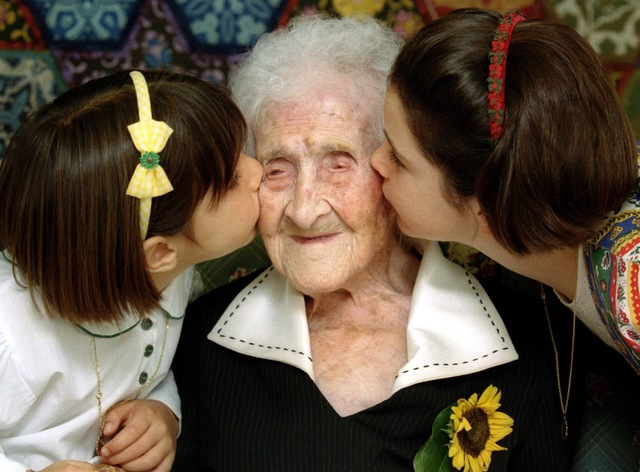 The world's oldest woman at the time, Jeanne Calment, 120 years old, is kissed by two young girls during a special ceremony in a retirement home in Arles, Southern France, Feb. 21, 1995.  (Jean-Pa ...