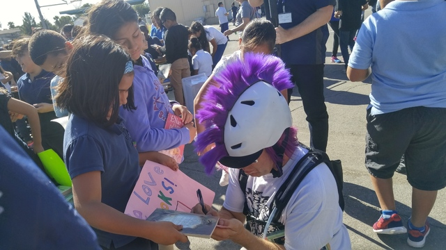 Gene Ward Elementary School students gather around a Ride for Reading volunteer bicyclist and ask for his autograph Sept. 22, 2016. The school received 2,500 books for their students and their lib ...