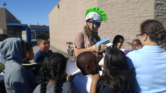 Gene Ward Elementary School students gather around a Ride for Reading volunteer cyclist to get his autograph during the Sept. 22, 2016, Ride for Reading event. The school received 2,500 books for  ...