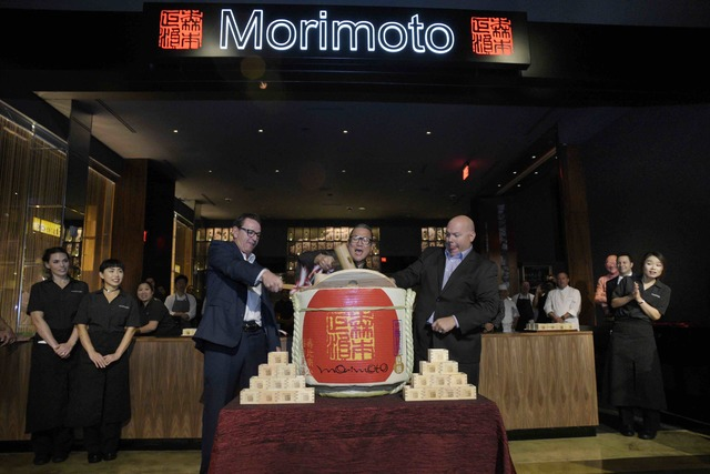 MGM Grand President and COO Scott Sibella, Masaharu Morimoto and MGM Grand Vice President of Food and Beverage Jason Shkorupa break open a cask of sake during the grand opening of Morimoto's first ...