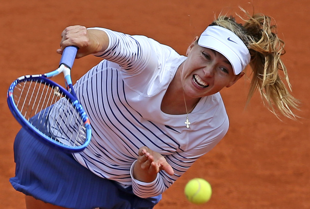 Russia's Maria Sharapova serves the ball to Lucie Safarova of the Czech Republic during the French Open in Paris,  June 1, 2015. The highest court in sports has cut Sharapova's two-year doping ban ...