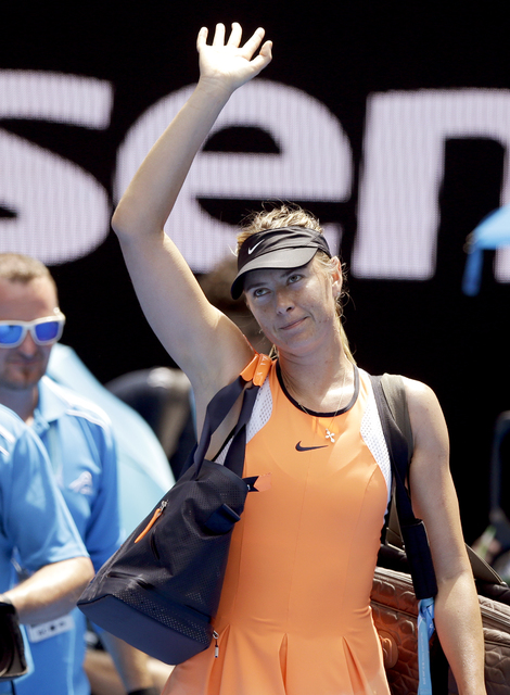Maria Sharapova of Russia waves as she leaves Rod Laver Arena following her quarterfinal loss to Serena Williams of the United States at the Australian Open tennis championships in Melbourne, Jan. ...