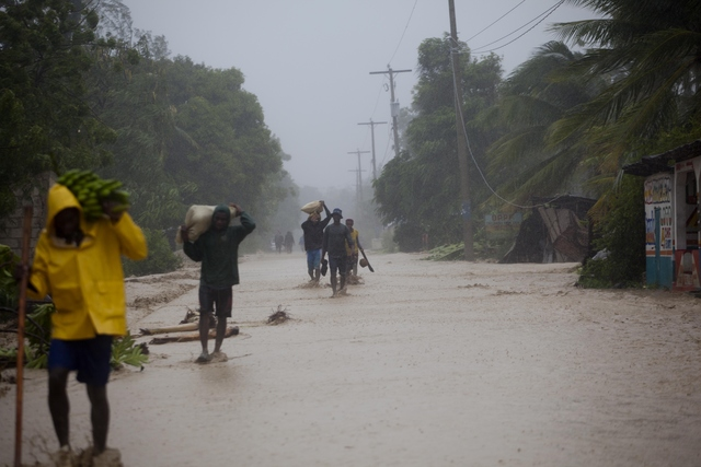 Residents walk in flooded streets as they return to their homes in Leogane, Haiti, Tuesday, Oct. 4, 2016. Matthew slammed into Haiti's southwestern tip with howling, 145 mph winds Tuesday, tearing ...