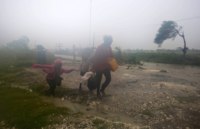 Residents head to a shelter in Leogane, Haiti, Tuesday, Oct. 4, 2016. Matthew slammed into Haiti's southwestern tip with howling, 145 mph winds Tuesday, tearing off roofs in the poor and largely r ...