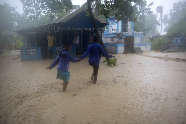 Residents wade through flood waters in Leogane, Haiti, Tuesday, Oct. 4, 2016. Matthew slammed into Haiti's southwestern tip with howling, 145 mph winds Tuesday, tearing off roofs in the poor and l ...
