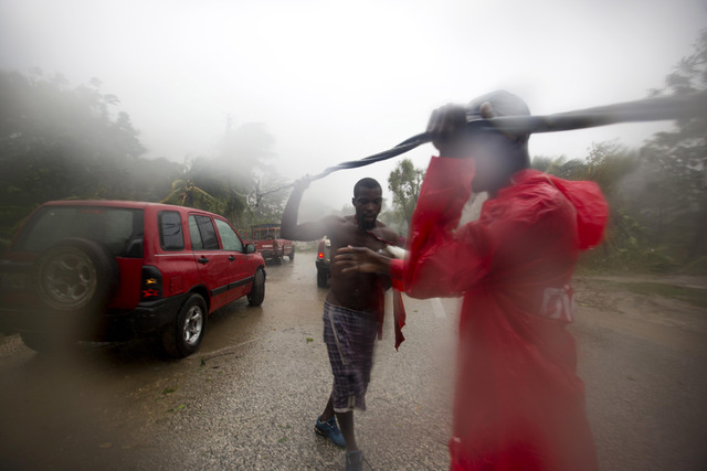 Two men remove a downed power line to allow vehicles to pass in Petit Goave, Haiti, Tuesday, Oct. 4, 2016. Matthew slammed into Haiti's southwestern tip with howling, 145 mph winds Tuesday, tearin ...