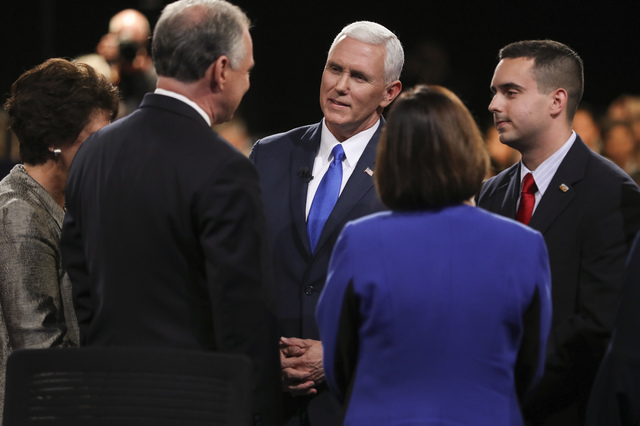Republican vice-presidential nominee Gov. Mike Pence and Democratic vice-presidential nominee Sen. Tim Kaine, left, talk after the vice-presidential debate at Longwood University in Farmville, Va. ...