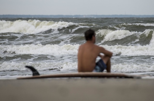 Eric Dunn sit on the northern end of Tybee Island's beach watching larger than average waves roll in as a result of approaching Hurricane Matthew, Tuesday, Oct. 4, 2016 in Tybee Island, Ga. Hurric ...