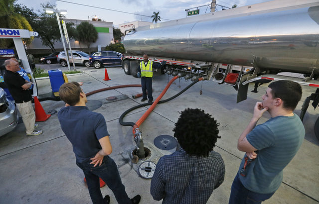 Motorists look on as Wayne Demps with CWC Transportation, center rear, fills the empty tanks of a Marathon gasoline station, Wednesday, Oct. 5, 2016, in Hollywood, Fla. Hurricane Matthew marched t ...