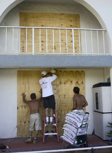 Paul Grimes, Lawrence Tanner and Ricky Corliss help board up apartments in advance of Hurricane Matthew on Wavecrest Avenue in Melbourne Beach, Fla., Wednesday, Oct. 5, 2016.  The building is just ...