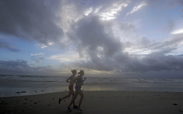 A pair of joggers run before sunrise along the surf of the Atlantic ocean Thursday, Oct. 6, 2016, in Daytona Beach, Fla. Forecasters said the first outer rain bands from Hurricane Matthew already  ...