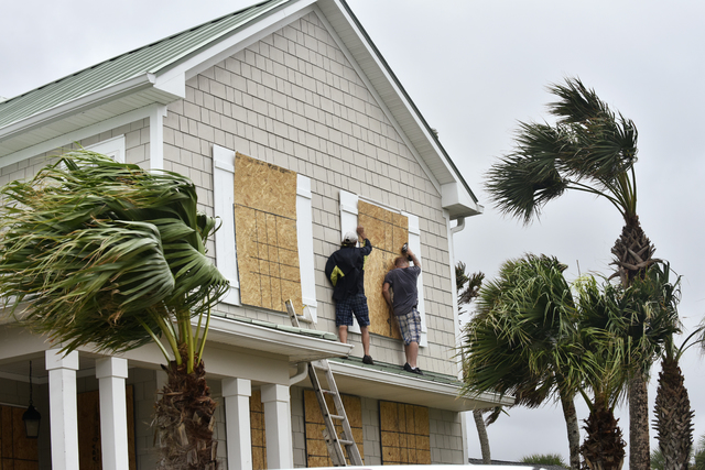 Workers from Armstrong Construction put plywood over windows of a home in preparation for Hurricane Matthew Wednesday, Oct. 5, in Ponte Vedra Beach, Fla. People boarded up beach homes, schools clo ...