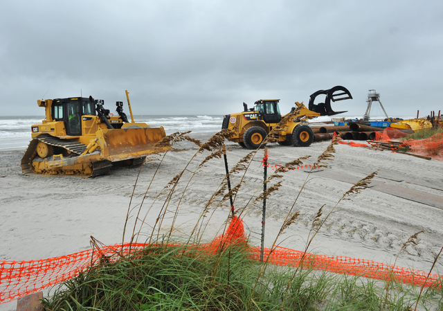 Workers remove pipes and other equipment related to a beach dredging project in preparation for Hurricane Matthew Wednesday, Oct. 5, in Jacksonville Beach, Fla. People boarded up beach homes, scho ...