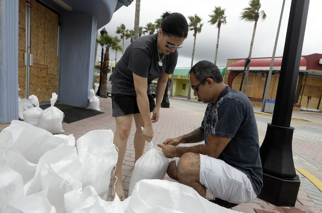 Miroslava Roznovjakova, left, and Ray Hayyat place sandbags in front of their store to guard against floodingThursday, Oct. 6, 2016, in Daytona Beach, Fla. Hurricane Matthew continues to churn its ...