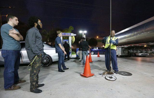 Motorists look on as Wayne Demps with CWC Transportation, right, measures the amount of gasoline he pumped into the tanks of a Marathon gasoline station, Wednesday, Oct. 5, 2016, in Hollywood, Fla ...