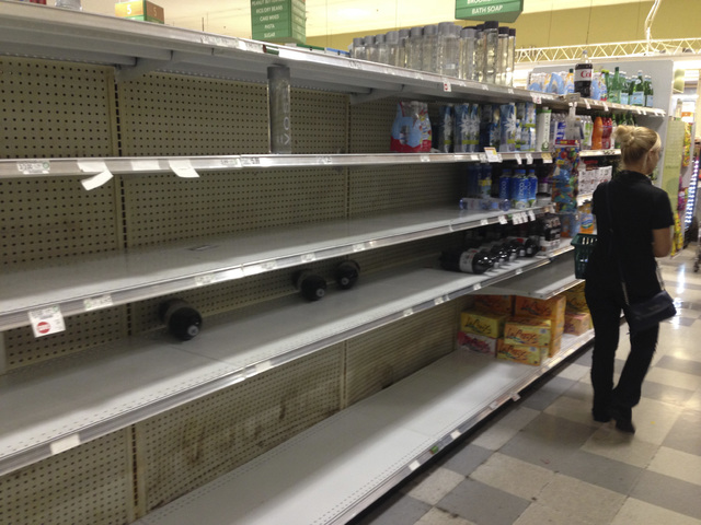 A shopper walks by the empty shelves where bottled water normally would be, Wednesday, Oct. 5, 2016, at a grocery store in Hollywood, Fla. Hurricane Matthew marched toward Florida, Georgia and the ...