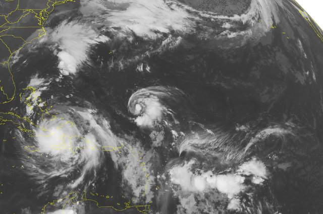 This NOAA satellite image taken Wednesday, Oct. 05, 2016, at 12:45 AM EDT shows both current active tropical cyclones in view moving away from the Caribbean, with Hurricane Matthew north of the ea ...