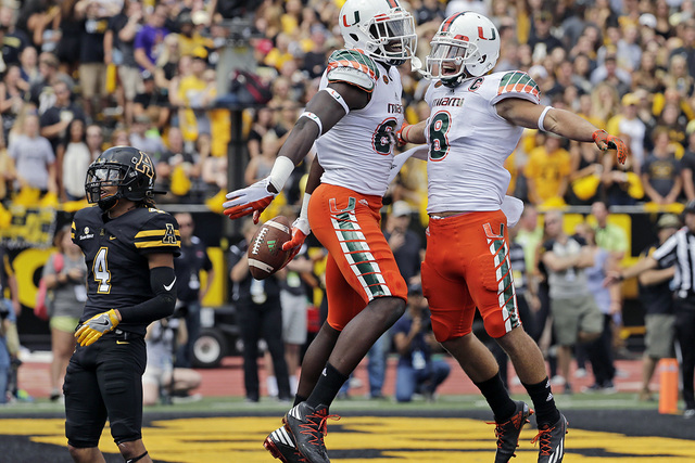 In this Sept. 17, 2016, file photo, Miami's David Njoku, center, celebrates with Braxton Berrios, right, after a touchdown catch as Appalachian State's Mondo Williams, left, watches during the fir ...