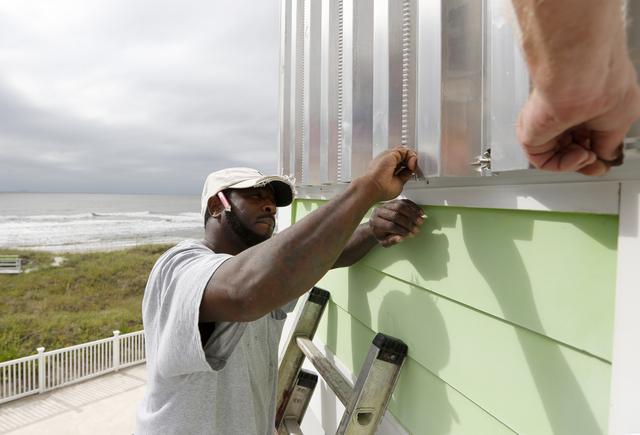 Dimitri Pinckney installs hurricane shutters in advance of Hurricane Matthew on the Isle of Palms, S.C., Wednesday, Oct. 5, 2016. Hurricane Matthew is expected to affect the South Carolina coast b ...