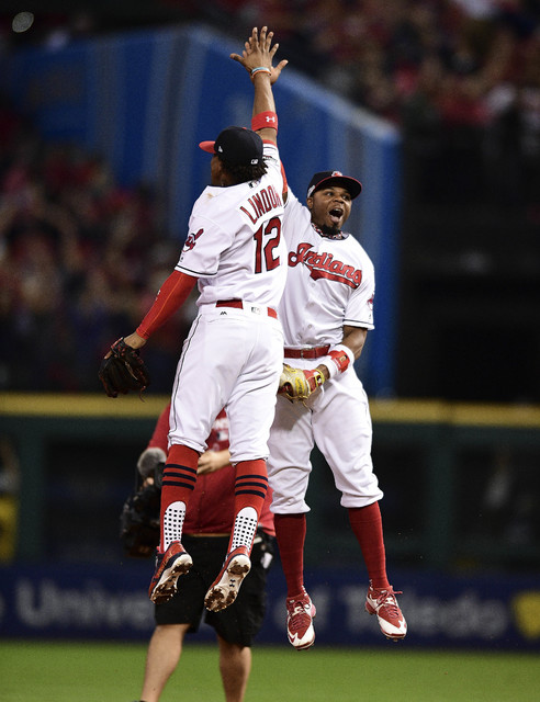 Cleveland Indians' Francisco Lindor (12) and Rajai Davis celebrate after the Indians defeated the Boston Red Sox 5-4 in Game 1 of baseball's American League Division Series, Thursday, Oct. 6, 2016 ...