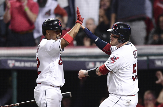 Cleveland Indians' Roberto Perez, right, celebrates with Francisco Lindor after scoring on a Jason Kipnis single against the Boston Red Sox in the fifth inning during Game 1 of baseball's American ...