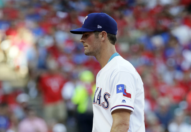 Texas Rangers starting pitcher Cole Hamels walks off the field after being pulled during the fourth inning against the Toronto Blue Jays in Game 1 of baseball's American League Division Series, Th ...