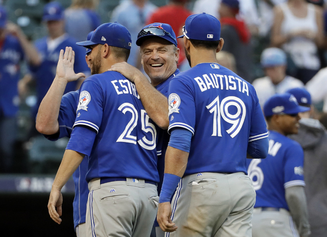 Toronto Blue Jays' Marco Estrada (25), manager John Gibbons, center, and Jose Bautista (19) celebrate the team's 10-1 win over the Texas Rangers in Game 1 of baseball's American League Division Se ...