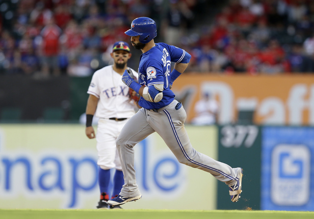 Toronto Blue Jays' Jose Bautista jogs past Texas Rangers second baseman Rougned Odor as Bautista rounds the bases on his three-run home run during the ninth inning of Game 1 of baseball's American ...