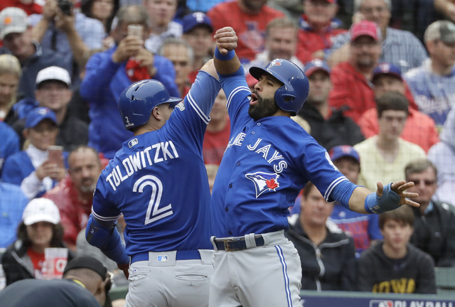 Toronto Blue Jays' Troy Tulowitzki (2) and Jose Bautista, right, celebrate Tulowitzki's two-run home run that scored Bautista in the second inning of Game 2 of baseball's American League Division  ...