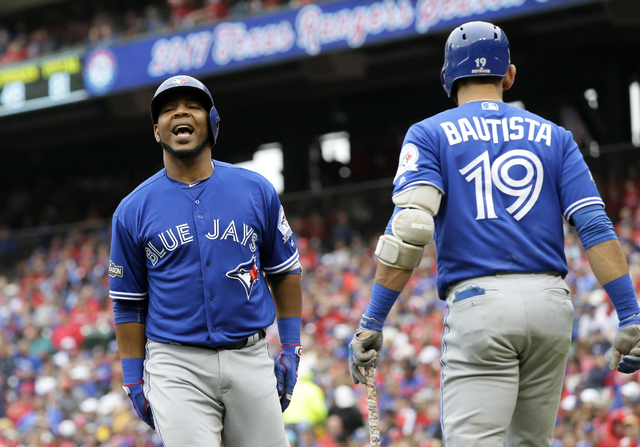 Toronto Blue Jays' Edwin Encarnacion, left, celebrates his solo home run with Jose Bautista (19) in the fifth inning of Game 2 of baseball's American League Division Series against the Texas Range ...